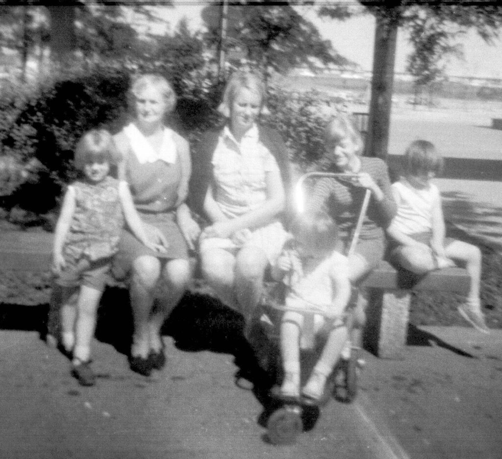 People on a bench, black and white photo.